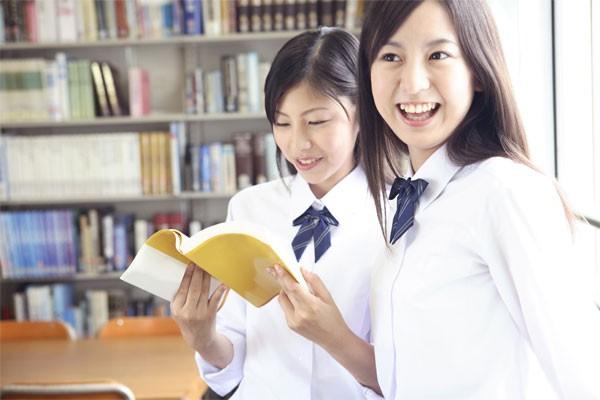 放課後に本で調べる高校生