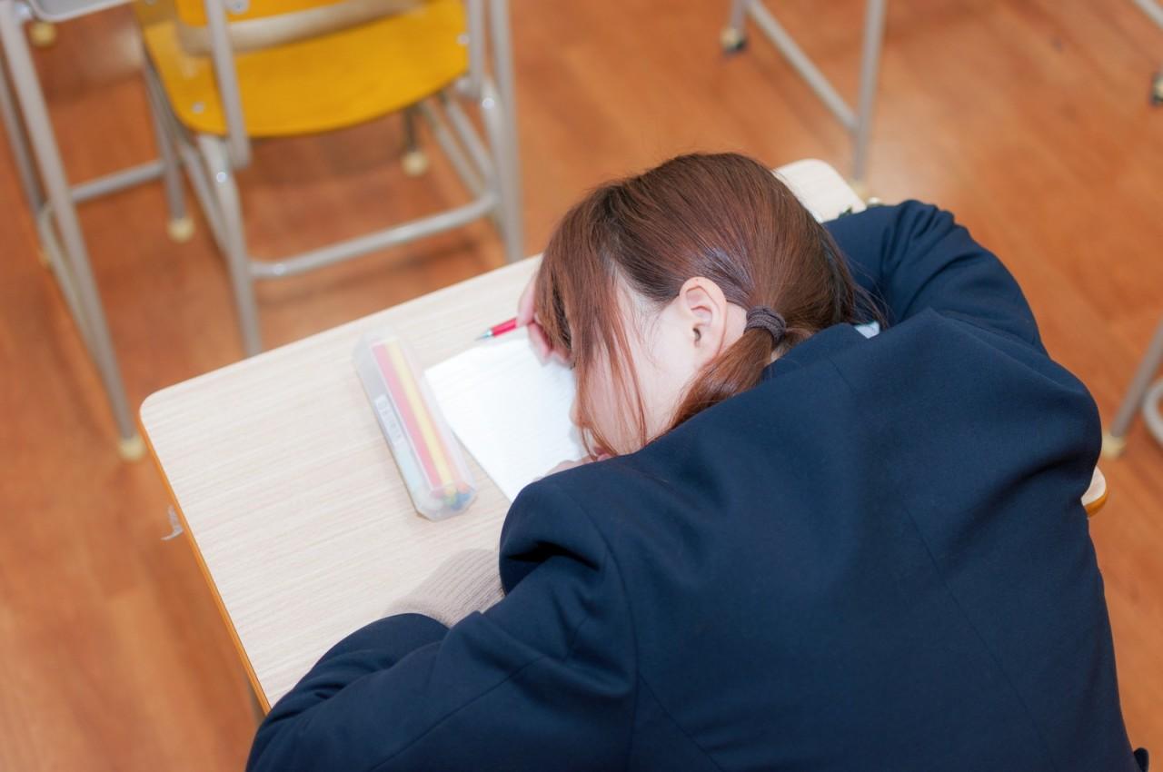 机に伏している受験生の画像です