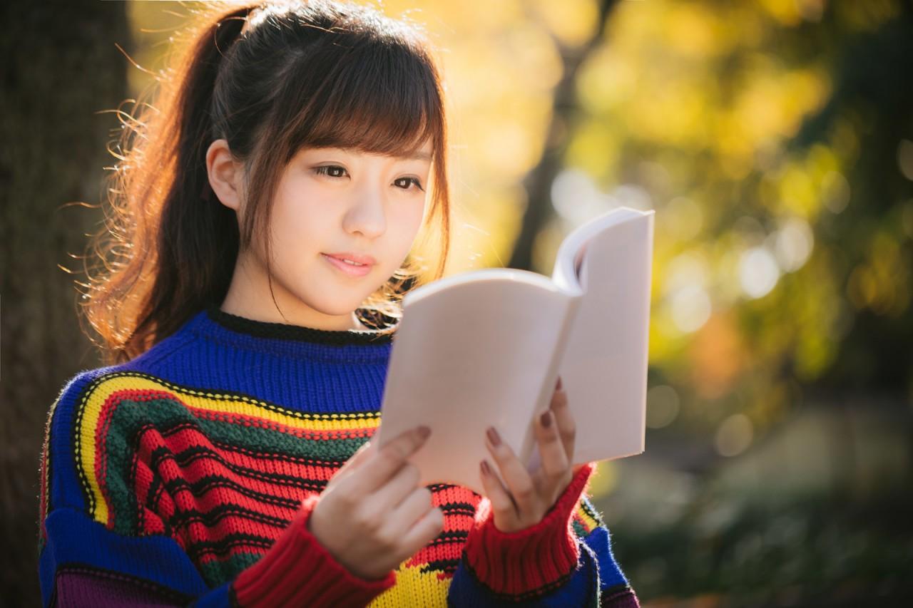 マルチカラーな服装で読書をする河村友歌
